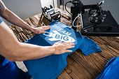 Man Printing On T Shirt In Workshop poster