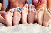 Soles of teenagers sunbathing on sandy beach