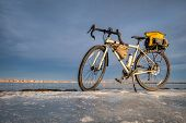 winter biking, touring or commuting - bicycle on an icy lake shore, Boyd Lake State Park in northern poster