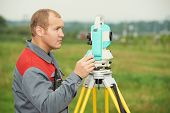 stock photo of geodesic  - One surveyor worker working with theodolite transit equipment at spring field construction site outdoors - JPG