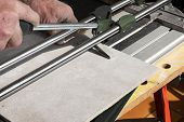 The Mason Cuts A Ceramic Tile With A Tile Cutter poster
