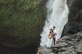Portrait Of Happy Pregnant Spanish Couple In Love With Amazing Waterfall View. Happy Together, Pregn poster