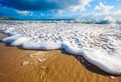 Waves wash over golden sand on Australian beach