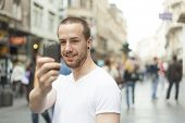 Men on street photographing with mobile phone, background is blured city