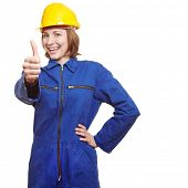 Cheering female worker in boiler suit showing thumbs up