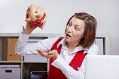 Shocked woman in office shaking a piggy bank
