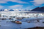 Tourist sightseeing boat. The lagoon Jokulsaurloun in Skaftafell Park. Iceland. Cold day in July. Wh poster