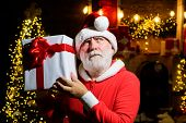 Serious Santa Claus Holds Present Box. Santa Claus Holds New Year Gift. Christmas Decoration. Merry  poster