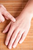 Acupressure, acupuncture point Hegu, LI4. Photo shows how to find this point.