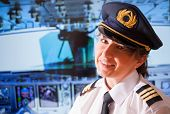 Beautiful woman pilot wearing uniform with epauletes, hat with golden wings sitting inside airliner with visible cockpit during flight.