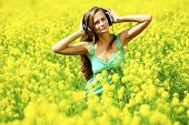 Young woman with headphones listening to music on oilseed flowering field