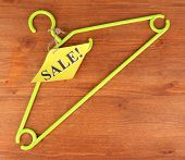 coat hanger with sale tag on wooden background