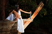 Woman on long tailed wooden boat holding a knife