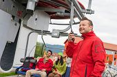 Man in red coat using radio starting chair lift
