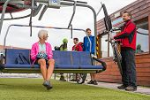 Happy couple sitting on chair lift man securing bicycle