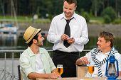 Smiling waiter taking order from men customers outdoor bar