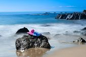 A beach goer's pink sunhat and towel rest on a rock along a beach in southern California.