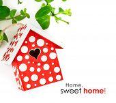 red birdhouse in white polka dot on green leaves