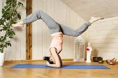 An image of a pretty woman doing yoga at home - Eka Pada Shirshasana