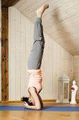 An image of a pretty woman doing yoga at home - Salamba Shirshasana