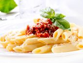 Pasta. Penne Pasta with Bolognese Sauce, Parmesan Cheese and Basil on served Table. Italian Cuisine.