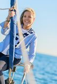 Happy Mature Woman Sitting On Boat Railing, Outdoors