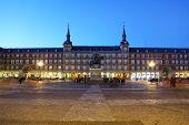 People walk near monument to Philip III Habsburg in Plaza Mayor at evening in Madrid, Spain.