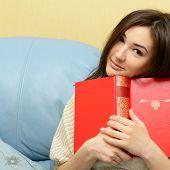 libro de lectura de chica alegre adolescente atractivo en el sofá en casa