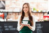 stock photo of apron  - Waitress holding cup of coffee in cafe - JPG