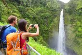 Couple tourists on Hawaii by waterfall. Tourist taking photo pictures of Akaka Falls waterfall on Ha