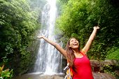 Hawaii woman tourist excited by waterfall during travel on the famous road to Hana on Maui, Hawaii.