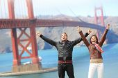 San Francisco happy people tourist couple at Golden Gate Bridge. Young attractive modern couple cheering happy, excited and joyful. California tourism concept with cheerful tourists.