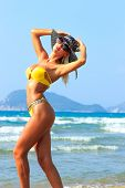 Beautiful young blonde fit woman in bikini on the beach