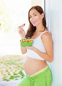 Happy pregnant woman eating healthy food, fresh fruit salad, pregnancy health care, happiness concept