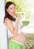 Cheerful young mother eating fruits, beautiful pregnant woman on the kitchen having healthy tasty lunch, new life concept