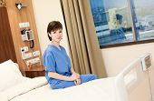 Positive female patient in blue gown sitting on hospital bed, looking at camera