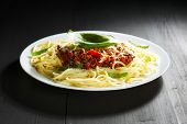 Spaghetti bolognese with basil in white plate on black table