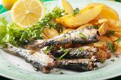 Grilled sardine fish with fried potato wedges