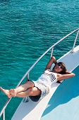Joyous Brunette Woman In Synglasses Laying On Shipboard Of Yacht