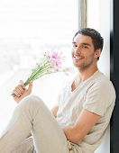 man sitting on the windowsill holding bouquet of flowers...