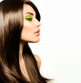 Hair. Beautiful Brunette Girl. Healthy Long Brown Hair. Beauty Model Woman with Green makeup. Trendy Spring Make-up