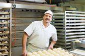 Male baker baking fresh bread rolls in the bakehouse