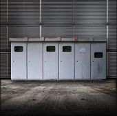Electric utility boxes in a facility. Facility or Base type of grungy interior, with metal siding wa