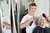 stock photo of hairspray  - Portrait of hairdresser using hairspray to style female client - JPG