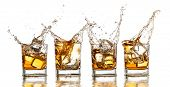 Whiskey glasses with splash, isolated on white background