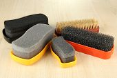 Set of stuff for cleaning and polish shoes, on wooden background