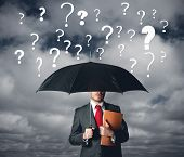 stock photo of interrogation  - A businbessman protects himself by doubts with umbrella - JPG