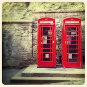 A pair of traditional British red phone boxes against the wall of Edinburgh Castle, Scotland. Cross
