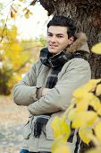 Young smiling man standing in autumn park.
