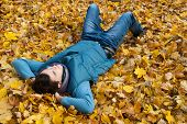 Young man laying in foliage in autumn park.